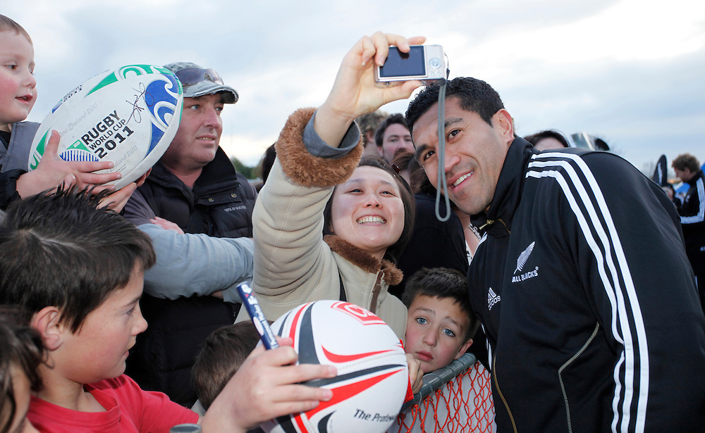 All Black Mils Muliaina having a photo taken with a supporter,  when the New Zealand All Blacks visited Centennial Park, Christchurch, New Zealand, Sunday, September 18, 2011.  Credit:SNPA / Pam Johnson