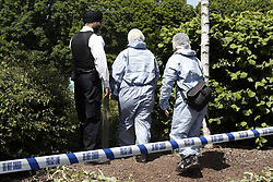 © Licensed to London News Pictures. 21/05/2019. London, UK. Police are seen on waste land next to a metal shed near Feltham in west London where a body was discovered. Reports say the victim was found next to a burnt out metal corrugated shed in the early hours of this morning. Photo credit: Peter Macdiarmid/LNP