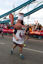 © Licensed to London News Pictures. 24/04/2016. London, UK. A fancy dress fun runner dressed in a beer bottle runs over Tower Bridge at the halfway point of the 2016 London Marathon.  Photo credit : Vickie Flores/LNP