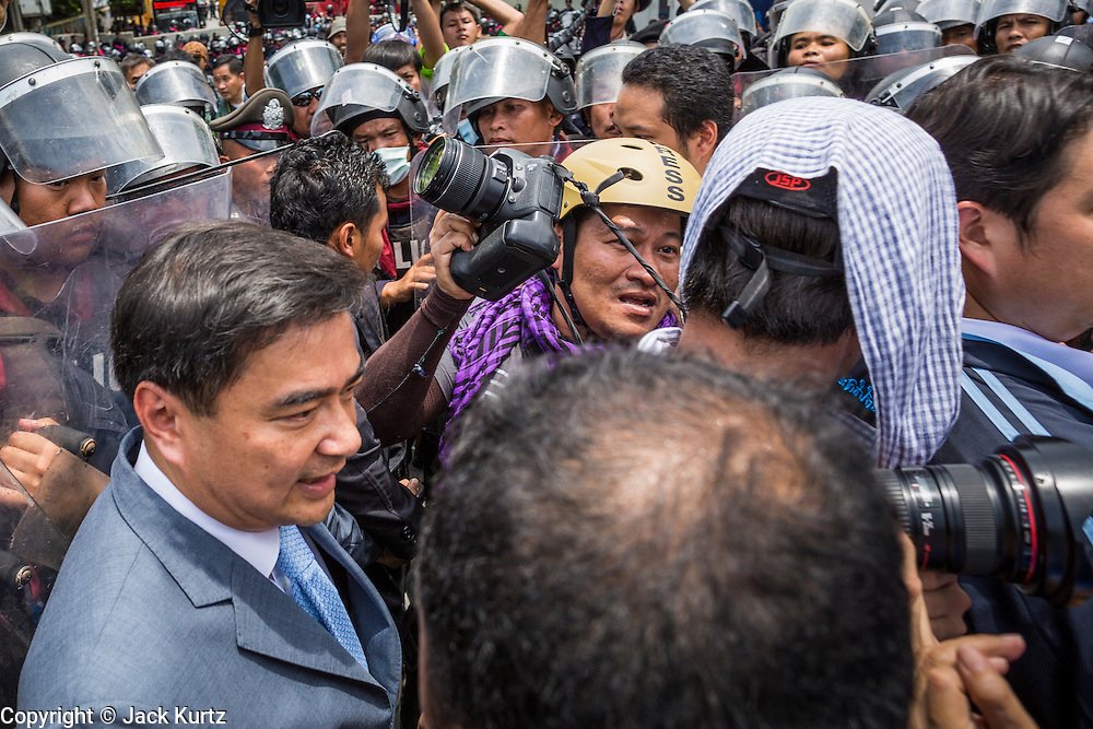 07 AUGUST 2013 - BANGKOK, THAILAND: Former Thai Prime Minister ABHISIT VEJJAJIVA, left, walks through a crowd of photographers and riot police to reach the Thai Parliament building during anti-amnesty protests in Bangkok. Abhisit's party, the Democrats, organized the anti-amnesty protest. About 2,500 protestors opposed to an amnesty bill proposed by Thailand's ruling party marched towards the Thai parliament in the morning. The amnesty could allow exiled fugitive former Prime Minister Thaksin Shinawatra to return to Thailand. Thaksin's supporters are in favor of the bill but Thai Yellow Shirts and government opponents are against the bill. Thai police deployed about more than 10,000 riot police and closed roads around the parliament. Although protest leaders called off the protest rather than confront police, a few people were arrested for assaulting police when they tried to break through police lines. Several police officers left the scene under medical care after they collapsed in the heat.    PHOTO BY JACK KURTZ