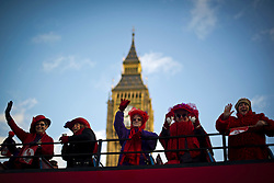 © London News Pictures. 01/01/2013. London, UK.  Members of the Red Hat Sociert, the largest women's social organization in the world, pass Big Ben on an open top bus as they take part in the 2012 New Years Parade through the centre London on January 1st, 2013. Photo credit : Ben Cawthra/LNP