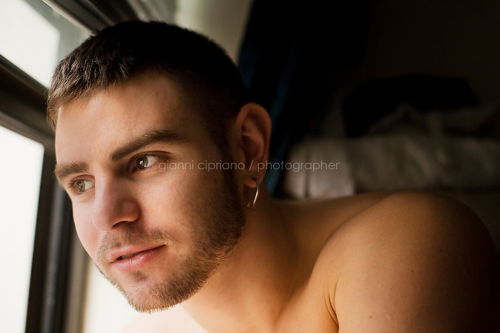 11 December, 2008. New York, NY. Daniel Alexander Osach (or Dan Alex), 24, is here at the window of his apartment in the Upper East Side after taking a shower. Dan Osach is a gay Go-Go dancer who grew up in New Haven, CT, and moved to New York a year ago. During the day he works for Christopher Hyland, Inc., a high-end fabrics purveyor. At night, he works as a Go-Go dancer in gay and women clubs around New York City. &quot;My life is work, gym, dance and sleep&quot;, Daniela says. Dan has a bachelor in English and majored in Poetry and Economics. After graduation in 2006 he worked as a store manager in a mall for 4 months in Connecticut. Tired and depressed of his job, he went to Florida to relax and then came to New York a year ago. He usually dances at &quot;The Cock&quot;, a  East Village gay bar. &quot;The Cock is not an institution. It's a landmark&quot; Daniel says. Daniel aspires to become maybe a teacher or to work for a travel magazine. &quot;What I would really love to do is to live my life laying down at the beach and reading poetry&quot;<br /> <br /> &copy;2008 Gianni Cipriano for The New York Times<br /> cell. +1 646 465 2168 (USA)<br /> cell. +1 328 567 7923 (Italy)<br /> gianni@giannicipriano.com<br /> www.giannicipriano.com