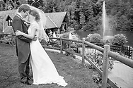 Bride and Groom standing facing each other with wedding venue in background. Photographed at Canada Lodge near Cardiff by Julian Hall Photography