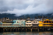 Afternoon light brightens the colorful buildings of a Monterey, California wharf, while dark clouds and heavy fog sweep through the forest hills in the distance