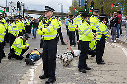 London, UK. 2 September, 2019. Activists locked on using an arm tube to block the road outside ExCel London on the first day of week-long protests against DSEI 2019, the world's largest arms fair. The first day of creative action was hosted by activists calling for a ban on arms exports to Israel and featured workshops, speakers, street theatre and dance. Israeli arms companies display weapons at DSEI marketed as 'combat-proven' following deployment against Palestinian communities.