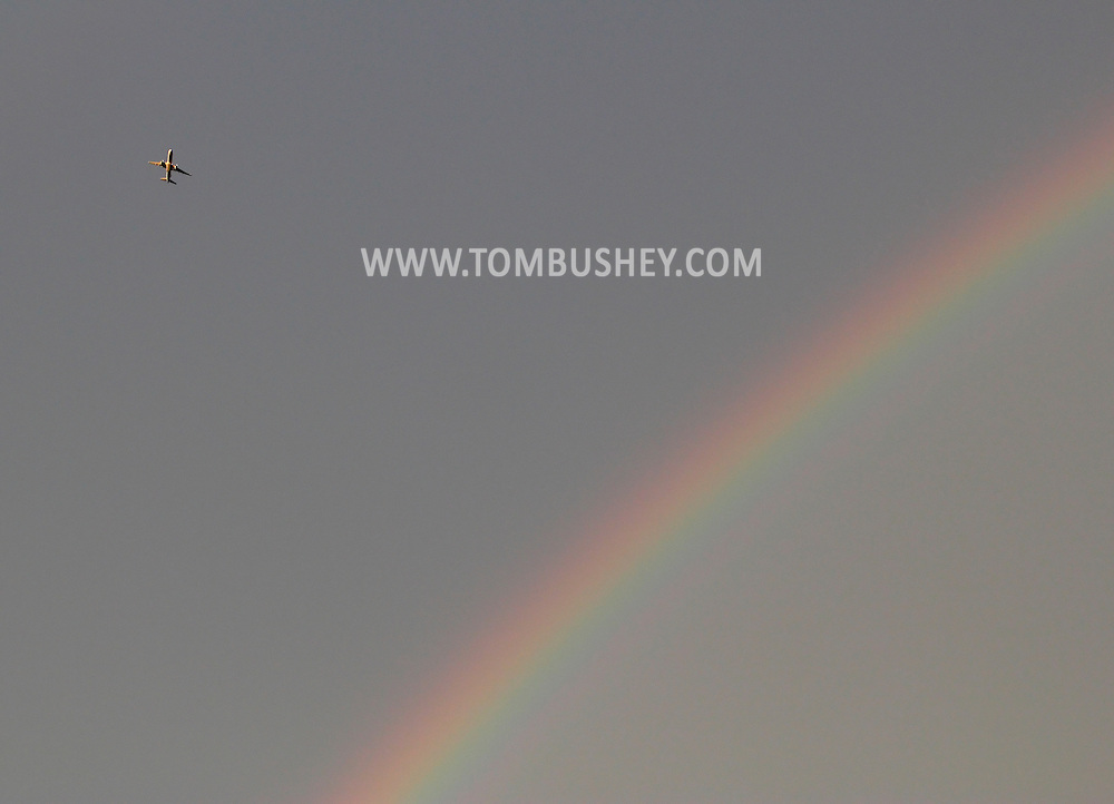 Scotchtown, New York - A jet airplane flies past a rainbow in the sky after a summer afternoon thunderstorm on Aug. 5, 2012.