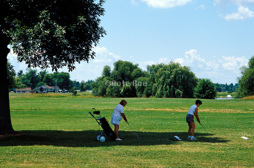 Two women practicing there golf swing on a driving range