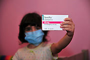 A young girl wears a medical face mask and holds a pack of Tamiflu tablets agaist Swine flu, October 30, 2009.