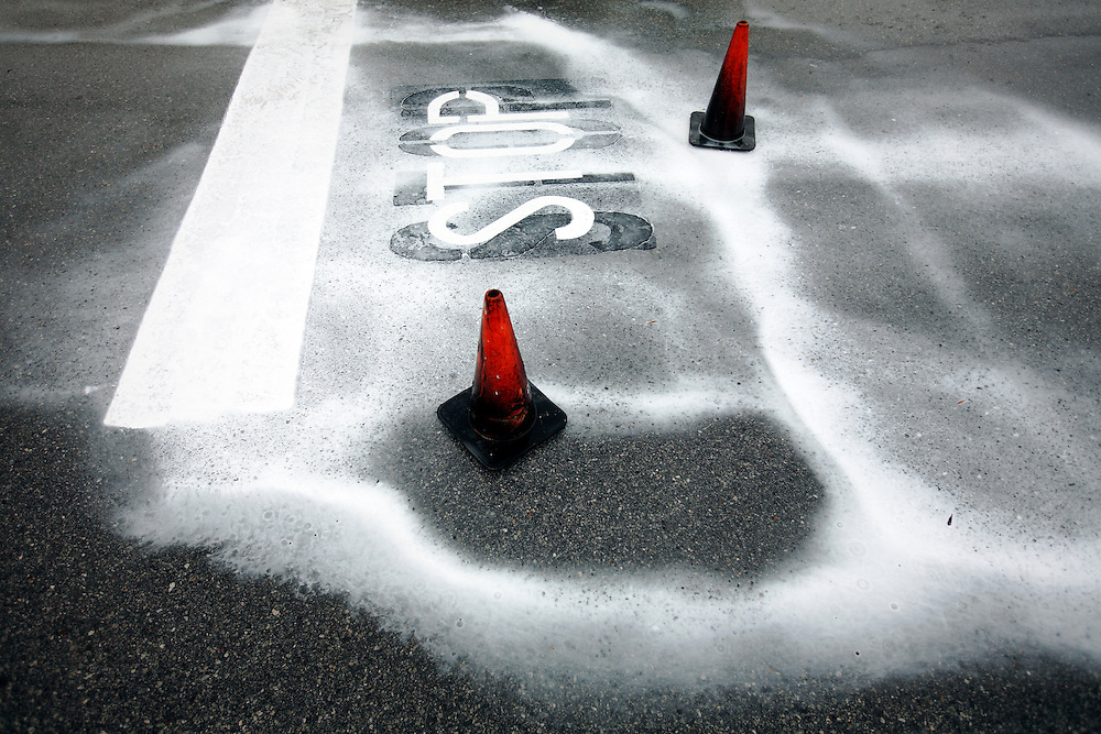Rain makes the paint of a freshly painted stop sign, marked off by cones, run over concrete in a parking lot.