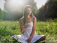 Young woman sitting in meadow cross-legged holding drinking glass
