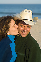 Man  in cowboy hat at the beach blushing as a girl kisses his cheek