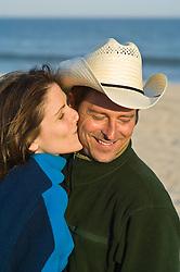 Man  in cowboy hat at the beach blushing as a girl kisses his cheek