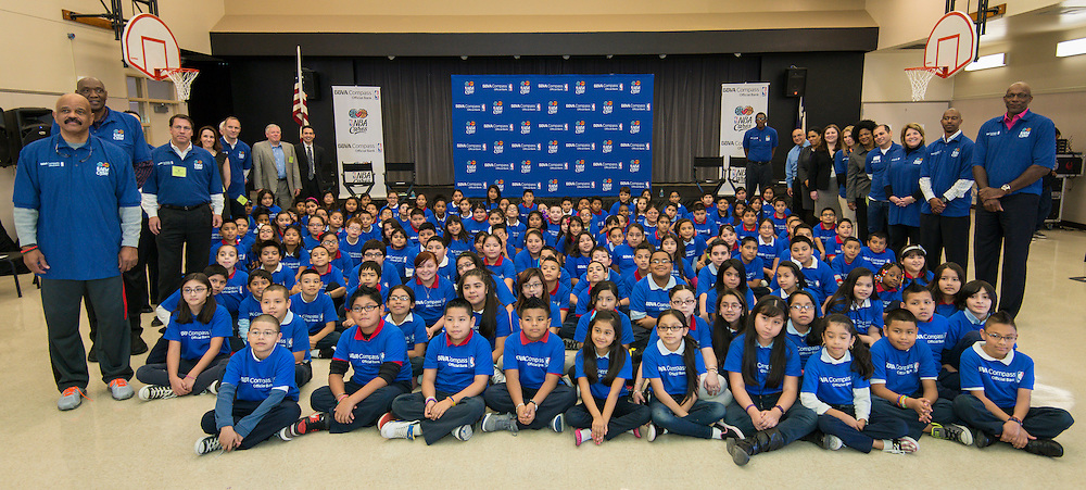 NBA legends and BBVA Compass staff pose for a photograph with students during a financial education and success program sponsored by NBA Cares and BBVA Compass at Crespo Elementary School, February 27, 2014.