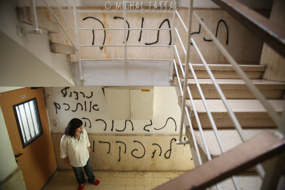 "Peggy Cidor, a leading woman of the Women of the Wall organization, stand in the hallway of her building in Jerusalem, Monday, May 20, 2013. The grafitti reads"" The women of the Western Wall are despised"". The group, known as ""Women of the Wall,"" convenes monthly prayer services at the Western Wall, the holiest site where Jews can pray, wearing prayer shawls and performing rituals that ultra-Orthodox Jews believe only men are allowed to do...Israeli officials initially opposed the group but have recently backed its right to worship. Earlier this month, thousands of ultra-Orthodox protesters tried to prevent their prayer service."