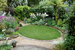 Brick edged oval lawn with curved borders and stone seat at Ladywood.