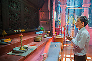 11 APRIL 2012 - HO CHI MINH CITY, VIETNAM:  People pray and burn incense at the Jade Emperor Pagoda in Ho Chi Minh City, Vietnam. It was built in 1909 by a Cantonese (Quang Dong) Congregation. It is one of the most colourful pagodas in HCMC, filled with statues of phantasmal divinities and grotesque heroes. Smoke of burning joss sticks fills the air, obscuring the exquisite woodcarvings decorated with gilded Chinese characters. The roof is covered with elaborate tile work, while the statues, which represent characters from both the Buddhist and Taoist traditions, are made of reinforced papier-mâché. The pagoda is dedicated to the Emperor of Jade, the supreme Taoist god. Ho Chi Minh City, formerly Saigon, is the largest city in Vietnam and the country's commercial center. It was the capital of South Vietnam before the reunification in 1975 and still shows more signs of American influence than northern Vietnam does.    PHOTO BY JACK KURTZ