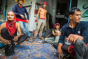 "12 DECEMBER 2012 - BANGKOK, THAILAND:  Demolition workers relax and share a bottle while they drink at the end of their shift in ""Washington Square"" a notorious entertainment district off Sukhumvit Soi 22 in Bangkok. Demolition workers on many projects in Thailand live on their job site tearing down the building and recycling what can recycled as they do so until the site is no longer inhabitable. They sleep on the floors in the buildings or sometimes in tents, cooking on gas or charcoal stoves working from morning till dark. Sometimes families live and work together, other times just men. Washington Square was one of Bangkok's oldest red light districts. It was closed early 2012 and is being torn down to make way for redevelopment.    PHOTO BY JACK KURTZ"