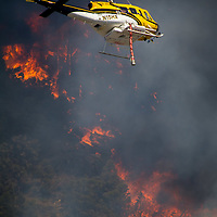 A fire fighting helicopter prepares to drop water on The Holcomb Fire as it burns in the Holcomb Valley are of the San Bernardino National Forest near Big Bear, Tuesday, June 20, 2017. Firefighters are battling a wildland fire north of Baldwin Lake in the Big Bear Lake area had charred 950 acres, and was 10 % contained. (EricReed/For The Souther California Newspaper Group)
