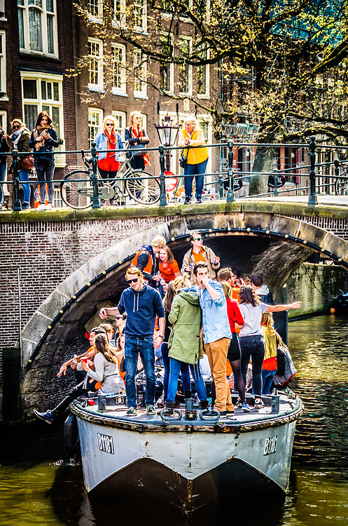 Boatful of people celebrating Koningsdag 2015 on the canals of Amsterdam.