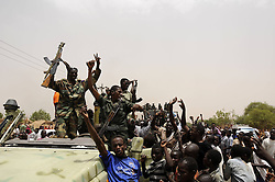 59722705.Soldiers wave to residents after returning from battlefield, in El Rahad of Sudan's North Kordofan State May 28, 2013. Sudanese army announced on Monday that it has liberated the strategic area of Abu Karshula in South Kordofan State from rebels of the Revolutionary Front. May 28, 2013..UK ONLY