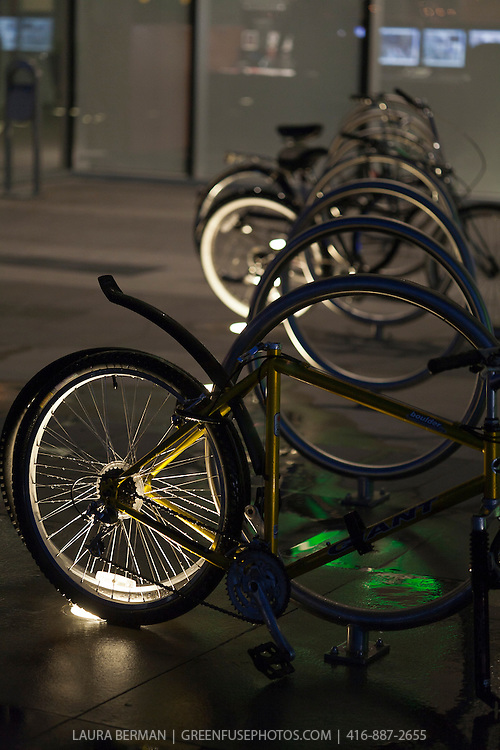 Bicycles at night in an urban courtyard, after a rain and lit by different colored lights.