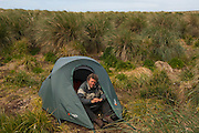 Pete Oxford camping.<br /> Kidney Island. Off of East Falkland. FALKLAND ISLANDS.<br /> Kidney Island is a small tussac-covered island lying at the southern entrance of Berkeley Sound. This is a government owned Reserve and is free of introduced animals and as it has not been used for pasturage retains its original flora.