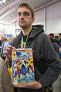 Manhattan, New York City, New York, USA. October 10, 2015. Comic book fan BRIAN GEPPNER, of Oswego, waits on line to have his Marvel Comics crossover, Fall of the Mutants X-Factor, autographed by its pencil artist Walter Simonson, right after it was autographed by its writer Louise Simonson, at the 10th Annual New York Comic Con. NYCC 2015 is expected to be the biggest one ever, with over 160,000 attending during the 4 day ReedPOP event, from October 8 through Oct 11, at Javits Center in Manhattan
