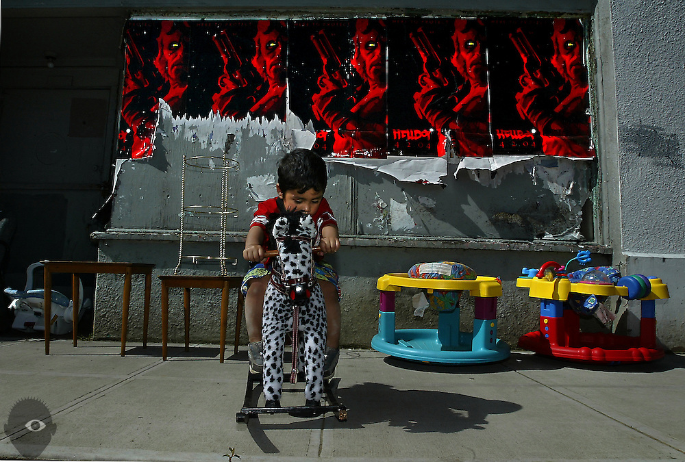 A collection of gun-wielding Hellboy's peer out from posters as a youngster enjoys a rocking horse for sale from his mother's shop in Portland, Oregon.