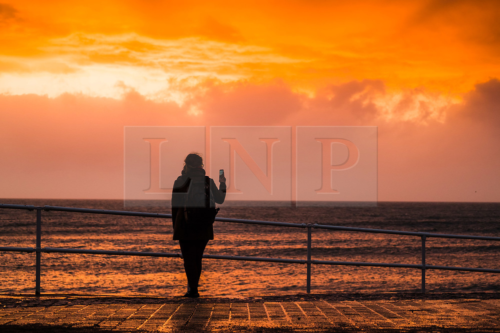 ©Licensed to London News Pictures. 26/04/2019<br /> A woman takes a selfie at the coast  as Storm Hannah, the latest named storm of the 2019 season begins to batter Aberystwyth . With winds expecting to gust at between 60 and 70mph overnight, there is a risk of damage to property and injuries. The Met Office has issued a yellow warning for strong winds covering much of the south if the UK from this evening until mid afternoon tomorrow<br /> Photo credit Keith Morris/LNP