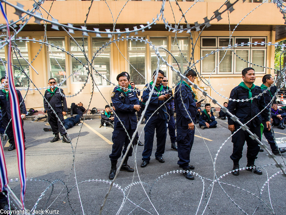04 DECEMBER 2013 - BANGKOK, THAILAND:  Thai riot police behind razor wire inside police headquarters during an anti-government protest Wednesday. Several hundred anti-government protestors tried to occupy Royal Thai Police Headquarters on Rama I Road in central Bangkok Wednesday. The protest was one of the continuing protests against the government of Prime Minister Yingluck Shinawatra. Police commanders allowed protestors to tear down police barricades and ordered riot police to lay down their shields. Protestors then chanted anti-government slogans and called on police to turn against the government before forming a motorcade and leaving the area. Anti-government protests have gripped Bangkok for nearly a month and protestors vow to continue their actions. Protests Wednesday were much smaller and more peaceful than protests earlier in the week.     PHOTO BY JACK KURTZ