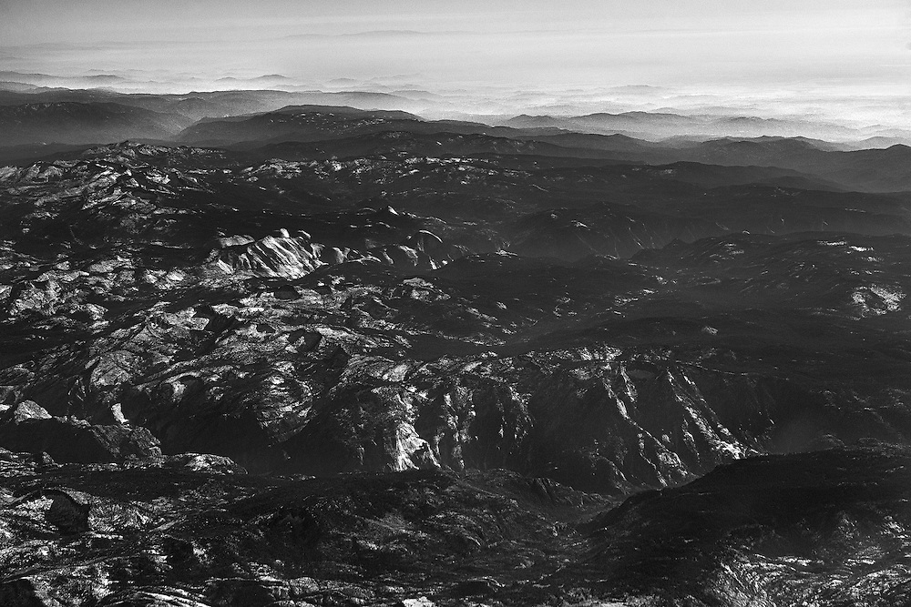Half Dome is seen in the distance from the air over the Sierras.