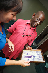 Elderly black man with white woman carer looking at old photo