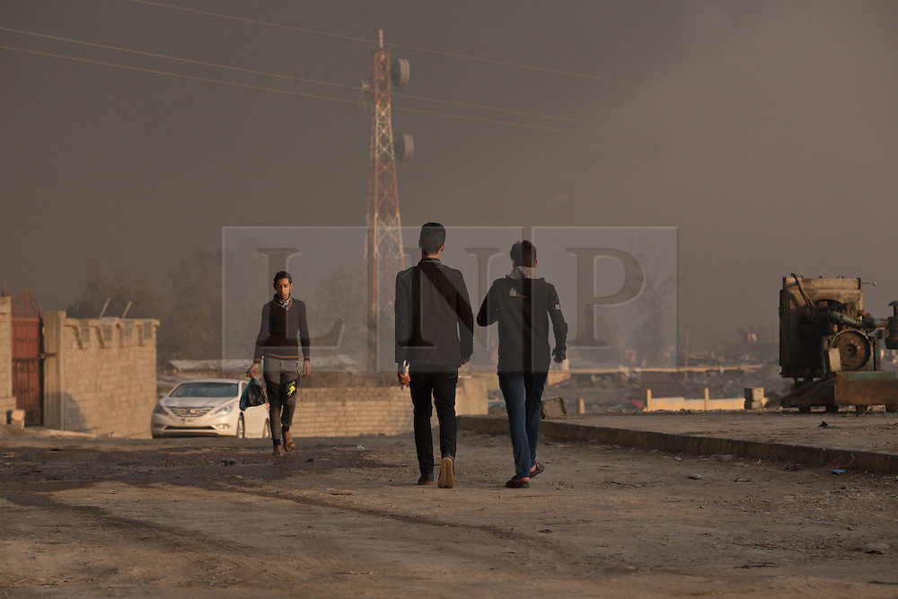 Licensed to London News Pictures. 02/11/2016. Qayyarah, Iraq. Civilians go about their daily lives under a cloud of smoke, coming from burning oil wells set alight by Islamic State militants, in the Iraqi town of Qayyarah, Iraq.<br /> <br /> Two months after being liberated from the Islamic State, the Iraqi town of Qayyarah, located around 30km south of Mosul, is still dealing with the environmental repercussions of their ISIS occupation. The town's estimated 15,000 inhabitants constantly live under, and in, heavy clouds of smoke which often envelope the settlement. The clouds emanate from burning oil wells in a nearby oil field that were set alight by retreating ISIS extremists after a two year occupation. The proximity of the fires, often right next to homes within the town, covers many buildings and residents with thick soot and will lead to long term health and environmental implications. Photo credit: Matt Cetti-Roberts/LNP