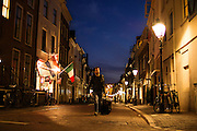 Een man loopt 's avonds met bagage door de Lange Smeestraat in Utrecht.<br />