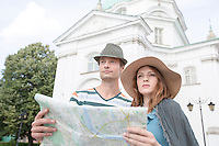 Tourist couple holding map outside St. Casimir Church; Warsaw; Poland