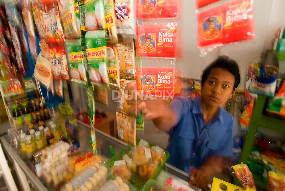 "A shop vendor in Mbah Maridjan's home town reaches for ""Kuku Bima"", a sports drink made from seahorses. As Mbah Maridjan's fabled stand-off with authorities gained national acclaim in 2006, manufacturers of Kuku Bima secured a contract with the volcano wizard for product endorsements. The deal that paid Rp80,000,000 (about US$9000) vastly overshadowed Maridjan's monthly salary of Rp8,000 (less than a dollar) to keep Mount Merapi in check. A portion of the endorsement proceeds were immediately turned over to each head of household in Maridjan's village. As an aside, when climbing Merapi, Maridjan did not take up this journalist's offer for a Kuku Bima energy drink."