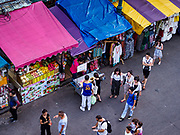 24 JULY 2018 - BANGKOK, THAILAND:  Tourists walk past street stalls on Khao San Road in Bangkok. Khao San Road is Bangkok's original backpacker district and is still a popular hub for travelers, with an active night market and many street food stalls. The Bangkok municipal government plans to shut down the street market by early August because city officials say the venders, who set up on sidewalks and public streets, pose a threat to public safety and could impede emergency vehicles. It's the latest in a series of night markets and street markets the city has closed.   PHOTO BY JACK KURTZ