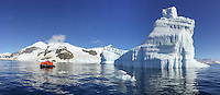Sun reflecting off the water with sculpted tabular icebergs grounded near Cuverville Island, Antarctica.
