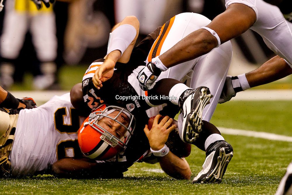 Oct 24, 2010; New Orleans, LA, USA; Cleveland Browns quarterback Colt McCoy (12) is sacked by New Orleans Saints linebacker Jo-Lonn Dunbar (56)and defensive end Will Smith (91) during a game against the New Orleans Saints at the Louisiana Superdome. The Browns defeated the Saints 30-17.  Mandatory Credit: Derick E. Hingle