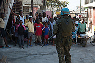 A Brazilian UN peacekeeper, facing wary community members, stands guard over a UN-led arrest operation in the Cité-de-Dieu neighborhood. Port-au-Prince, February 2, 2008.