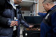 "Michael ""Panini"" warms his hand over Willie Torres' grill in Staten Island, N.Y. Nov. 2, 2012. Torres grilled for neighbors as they gutted their homes in the hard hit neighborhood of South Beach following Hurricane Sandy."