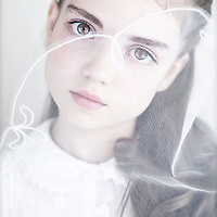 Young girl with brunette hair looking through gauze at camera