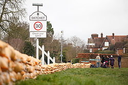 © Licensed to London News Pictures. 10/02/2014. Datchet, Berkshire, UK. A group of residents standing near a sand bag flood defence to prevent people taking sandbags away. Flooding in Datchet today, 10th February 2014 after the River Thames burst its banks. Photo credit : Rob Arnold/LNP