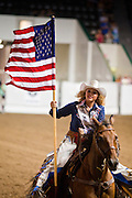 "01 SEPTEMBER 2011 - ST. PAUL, MN:  A woman on horseback carries the American flag around the arena at the opening of a high school rodeo performance at the Minnesota State Fair. The Minnesota State Fair is one of the largest state fairs in the United States. It's called ""the Great Minnesota Get Together"" and includes numerous agricultural exhibits, a vast midway with rides and games, horse shows and rodeos. Nearly two million people a year visit the fair, which is located in St. Paul. PHOTO BY JACK KURTZ"