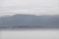 Newburgh, New York - Fog covers the Hudson River and clouds cover the tops of the Hudson Highlands, including Mount Beacon, on the east side of the river on a warm winter day on Jan. 2, 2010.