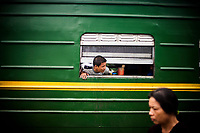 A man pokes his head out of the train window in Vietnam.