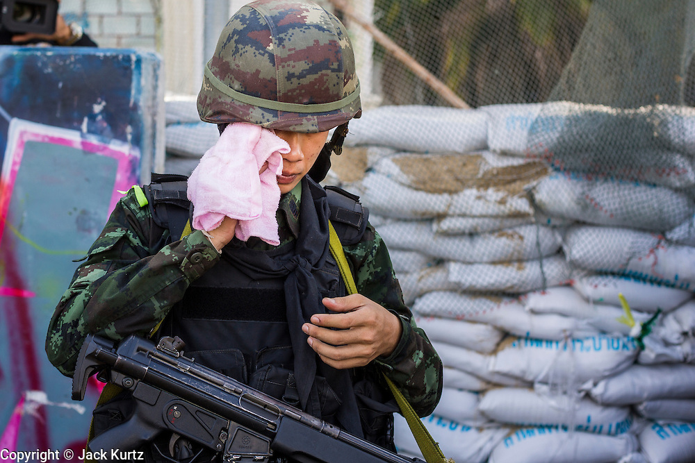 23 MAY 2014 - BANGKOK, THAILAND: A Thai soldier wipes his brow while on duty at a checkpoint in the Dusit district in Bangkok. The Thai military seized power in a coup Thursday evening. They suspended the constitution and ended civilian rule. This is the 2nd coup in Thailand since 2006 and at least the 12th since 1932. The army has ordered both anti-government protestors in Bangkok and pro-government protestors in the suburbs to go home and arrested leaders of both groups.    PHOTO BY JACK KURTZ