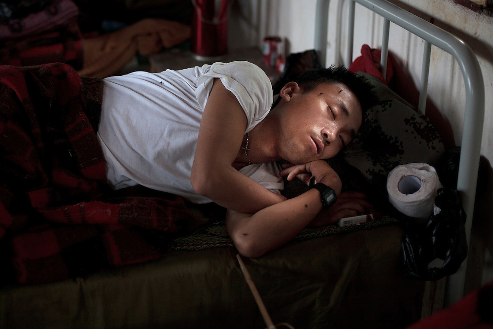 Kachin's militia member Lalaw Ze Dai, from Waimaw village, 25, sleep in his bed in the Military General Hospital in Laiza village close to the China border, Myanmar on July 20, 2012.  He was injured by a landmine in June, 26, 2012 loosing part of his right leg on top of knee.