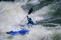 Kayaker paddling through white water Rapids