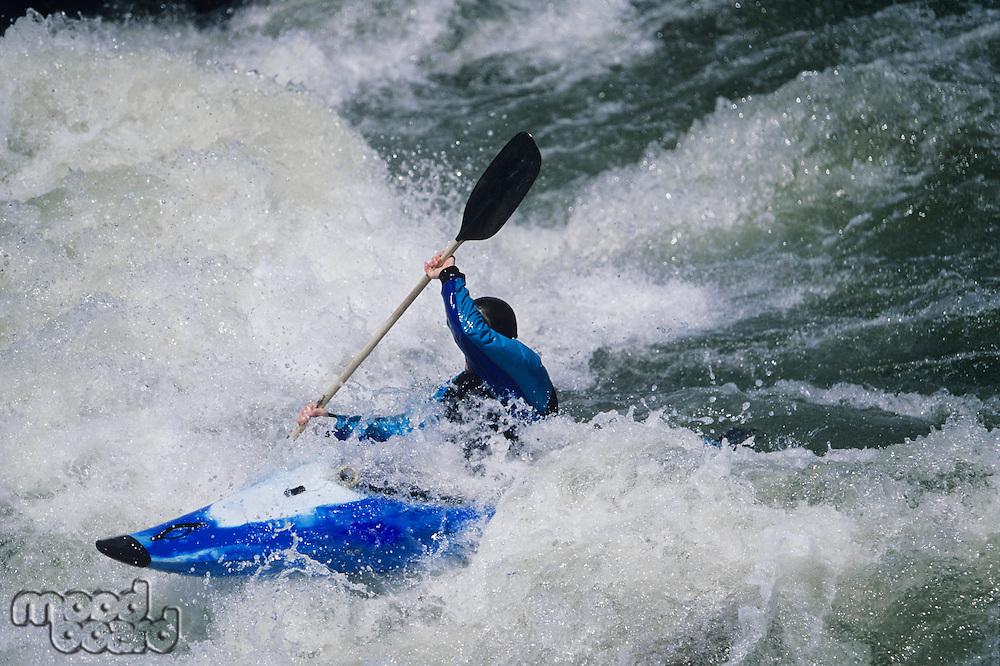 Kayaker paddling through white water Rapids